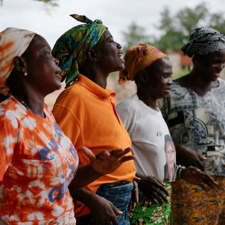 Women in northern Ghana, stood in a row smiling and dancing.