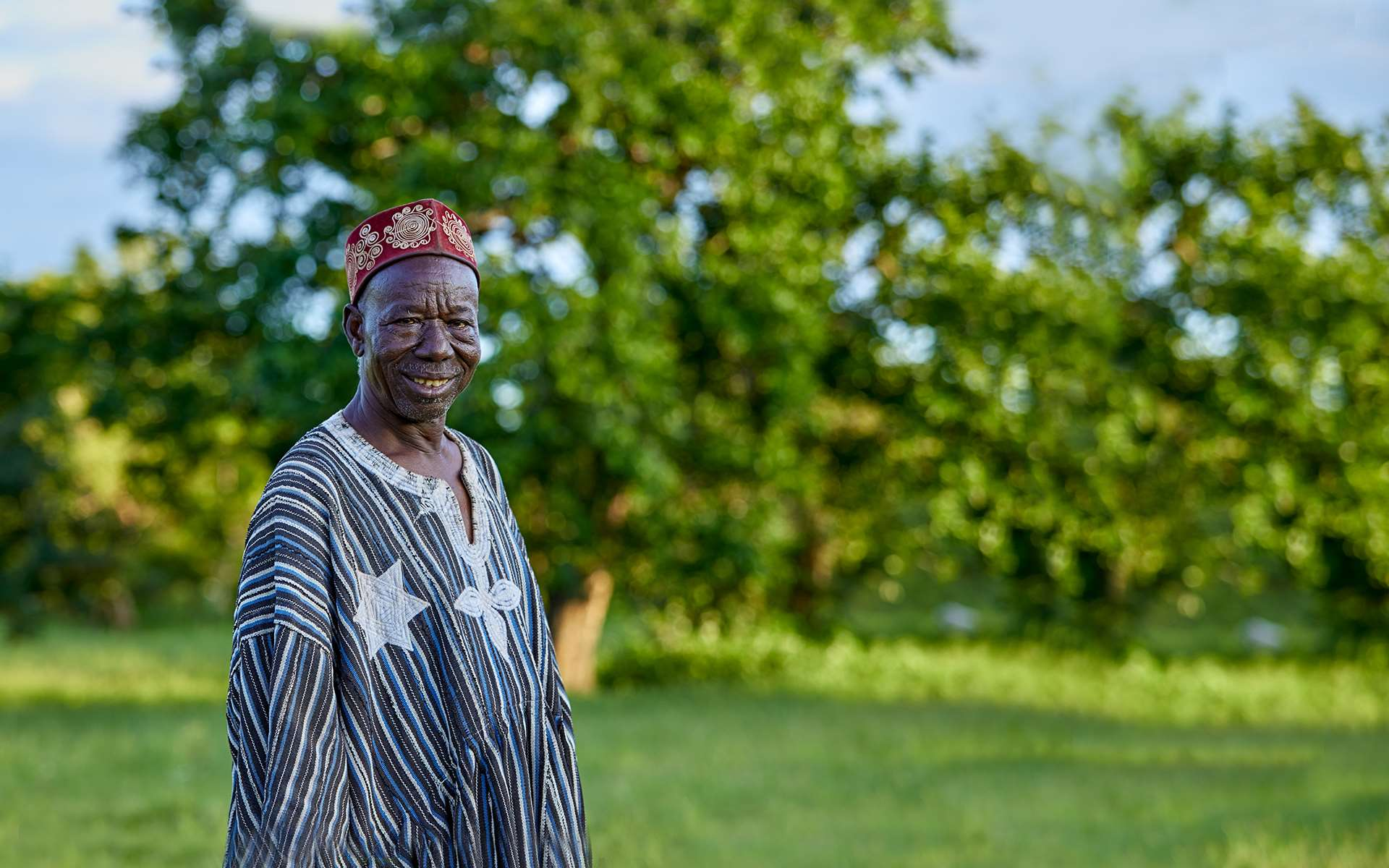 Kazigu, a lead farmer on a Tree Aid project and chief of the village, smiling in front of trees.