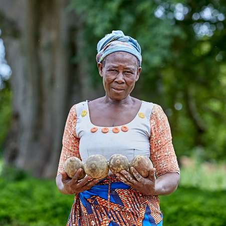 Aweliwo, a woman living in northern Ghana, smiling and holding baobab fruits that she will process and sell to earn an income.