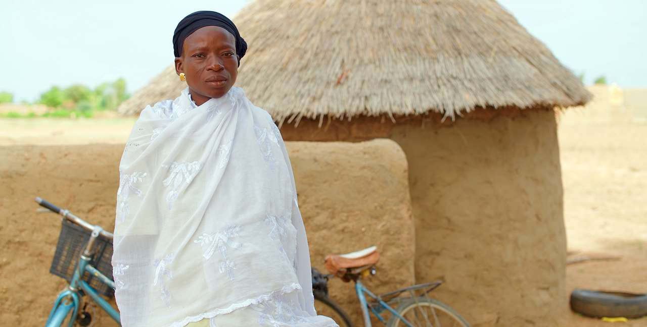 Bibata, a member of a soumbala enterprise group, standing in front of her home.