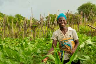 Gifty, a mother in Ghana, smiling as she works on her farm tending to her crops.