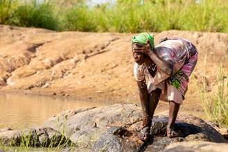 A women washing her face in the Daka river in Ghana.