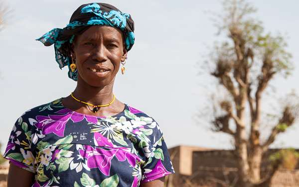 Habi,  a woman we are working with in Mali, smiling in front of her village.