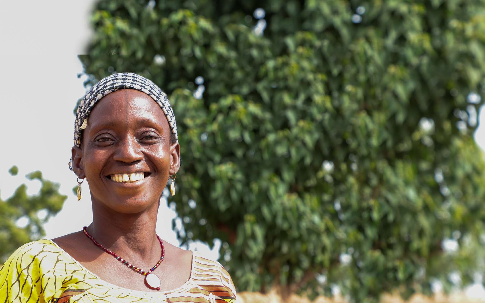 Djamako, a woman on Tree Aid's She Grows project, smiling in front of trees.