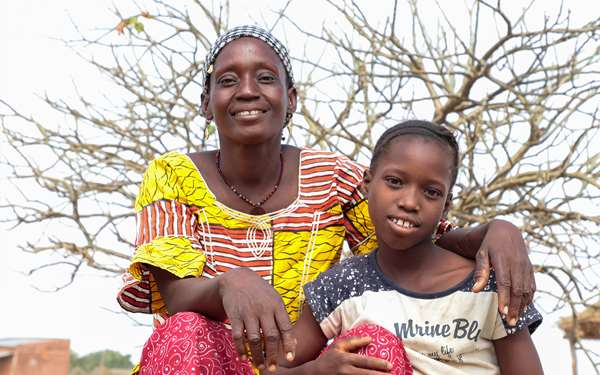 Djamako, a woman on Tree Aid's She Grows project, smiling with her daughter.