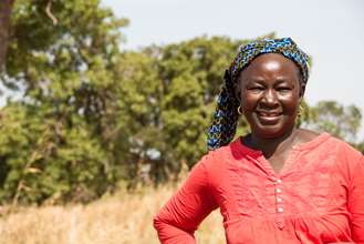 A women in Koulikoro in Mali standing and smiling in front of trees.