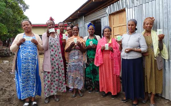 A women's enterprise group holding up their products that they will sell at market.