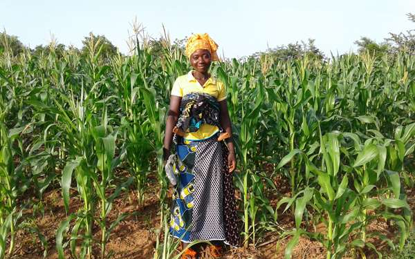 A women standing and smiling in her farm where she is growing crops for food and to sell.
