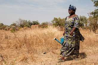 A women in Mali walking through her village with a watering can to tend to her trees.