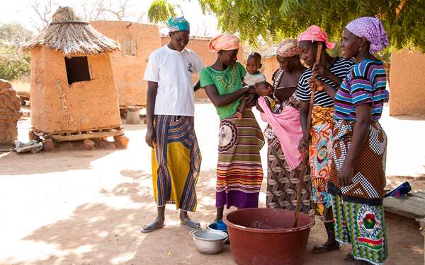 Women from a shea enterprise group in Mali standing round a bowl of shea butter which is being stirred.