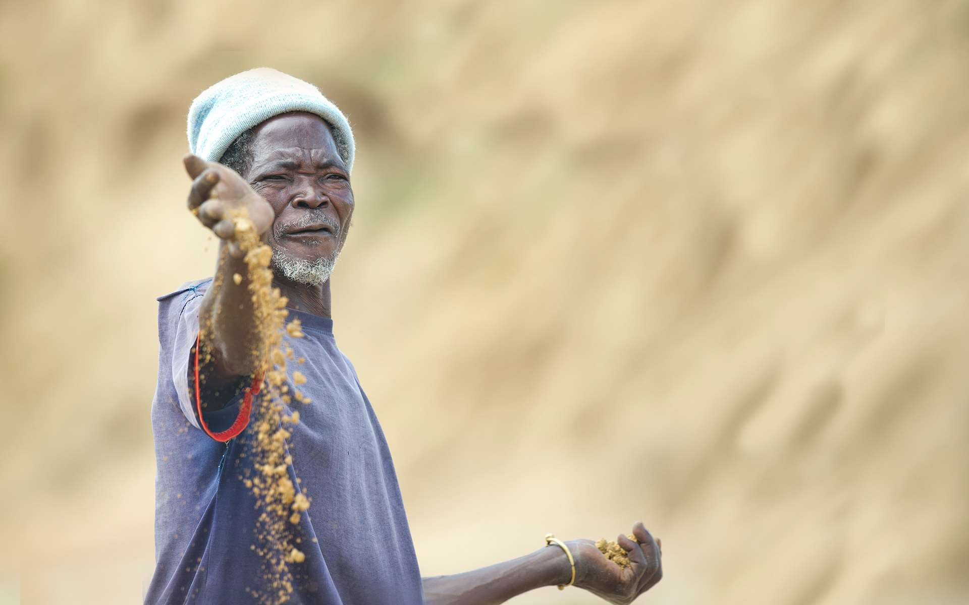 Mbole, a farmer in Ghana, holding up soil that has become so degraded that he can no longer farm on it. Photo credit, Rowan Griffiths, Daily Mirror.