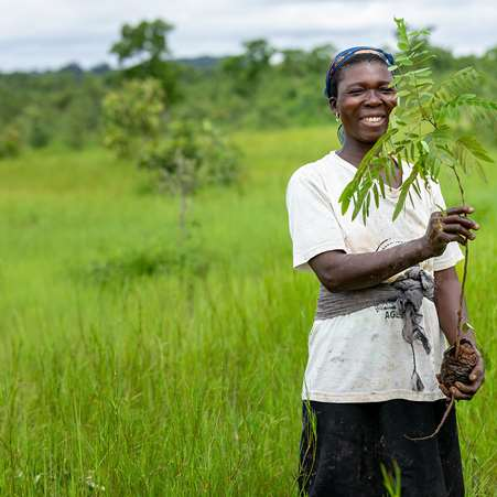 A woman in Ghana smiling and holding a tree sapling that she will plant along the Daka river as part of Tree Aid and Ecosia