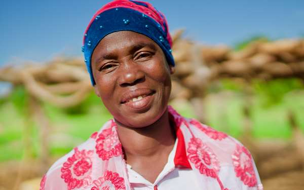 Petra, a member of a shea butter enterprise group in her village, smiling.