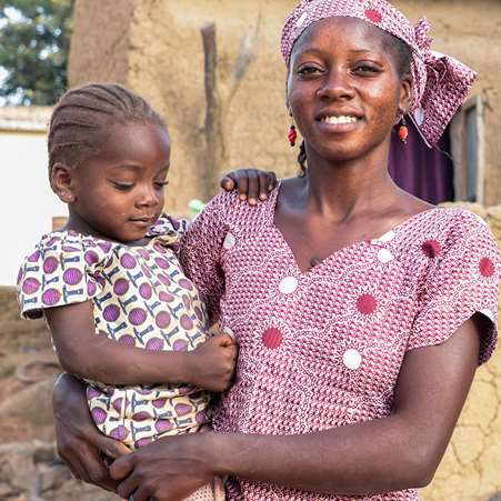 Sékoura, a woman on the She Grows project, holding her daughter in front of their house.