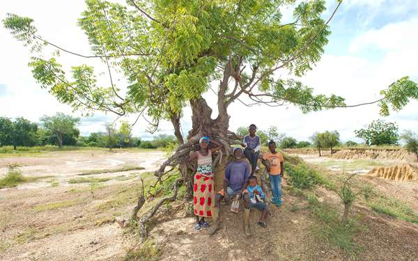 Mbole, a man in Ghana who is participating in a Tree Aid project, is sitting on degraded land with his family. Photo credit: Rowan Griffiths, Daily Mirror