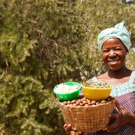 Anè, a women taking part in a Tree Aid enterprise project in Mali, holding a basket of shea nuts.