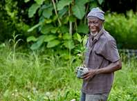 Soloman, the owner of a tree nursery in Ghana, smiling and holding tree saplings.