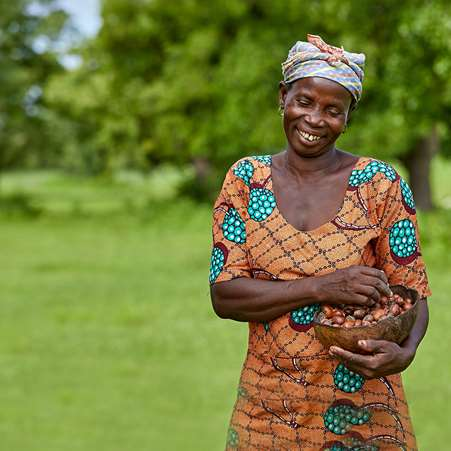 Kubaje, a women that Tree Aid is working with in Ghana, smiling and holding a bowl of shea nuts that she collected.