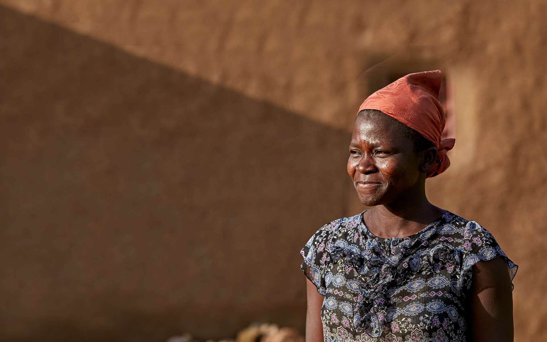 Kachana, a woman we are working with in Ghana, standing outside of her house in Nakolo village