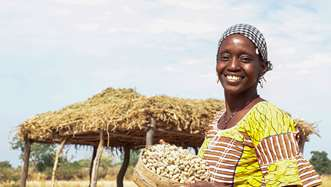 Djamako, a woman on Tree Aid's She Grows project, holding a bowl of peanuts that she farmed on her land.
