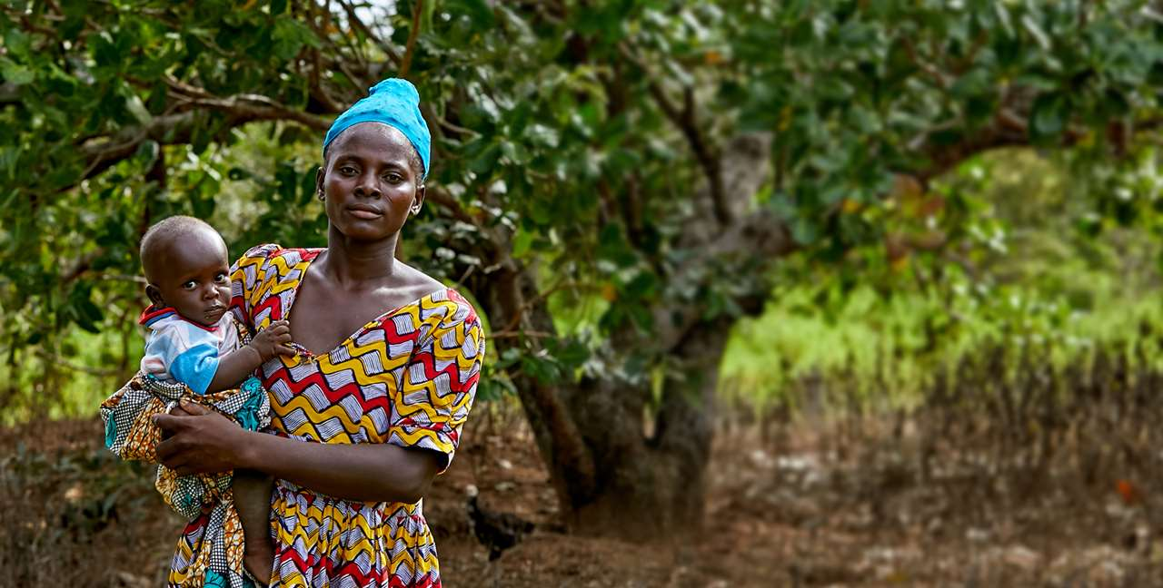 Gifty is holding her baby in front of a tree. She is being supported by a Tree Aid project to earn an income from cashew trees.