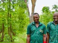 Two forest guards smiling in front of a forest.
