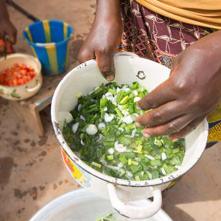 Close up of moringa leaves in a bowl being cooked up to feed a family.