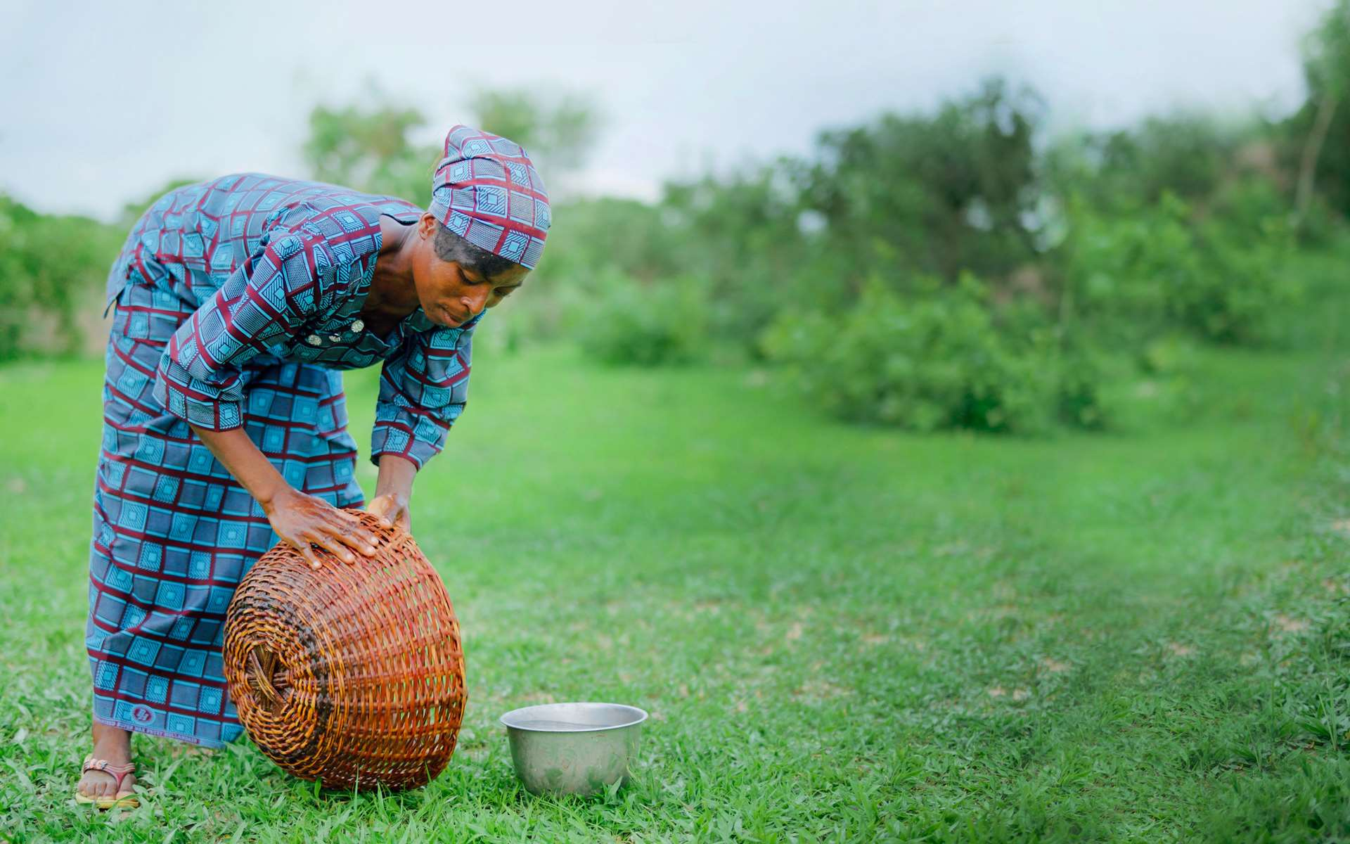 Kapouri, a woman in Burkina Faso, washing out a bowl used to collect shea nuts.