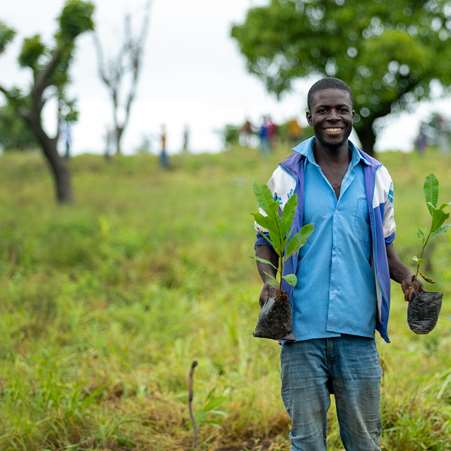 Francis, a man we are working with in Ghana, holding a tree sapling in each hand which he will plant in the community.