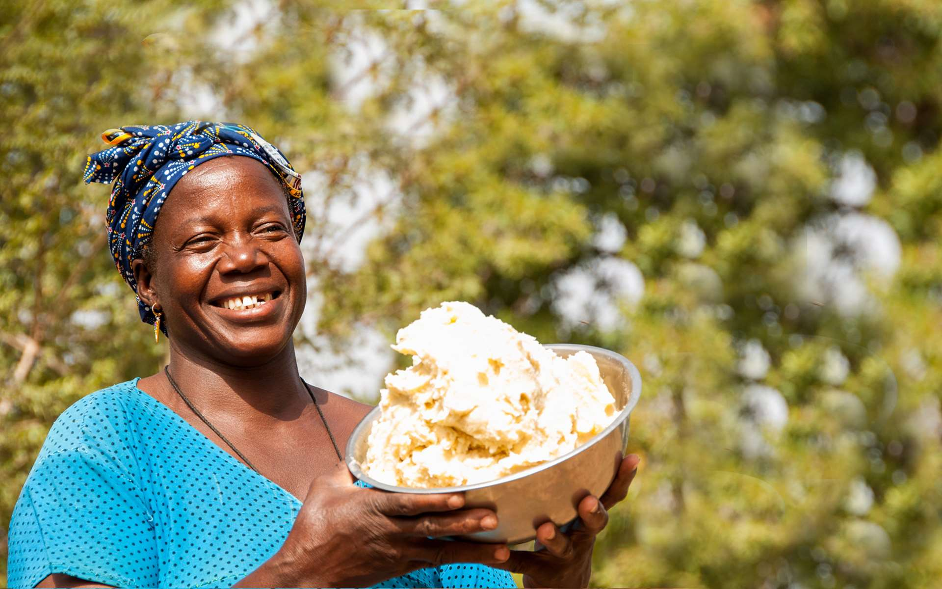 Bernadette, a member of a shea enterprise group set up through a Tree Aid project, holding shea butter and smiling.
