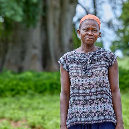 Kachana, a mother in Ghana, in front of a tree.