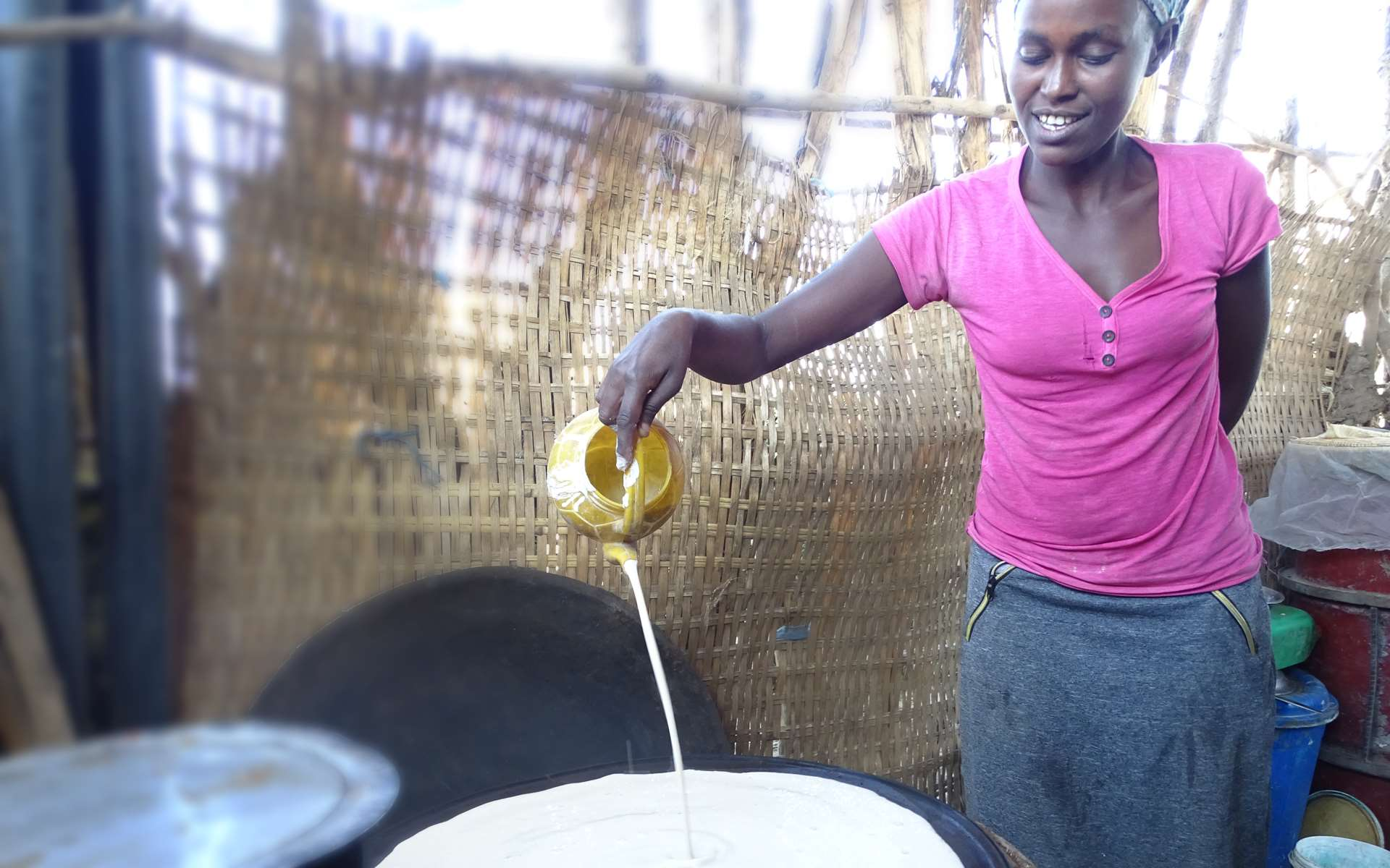 A woman in Ethiopia cooking injera on a fuel-saving stove that she received through a Tree Aid project.