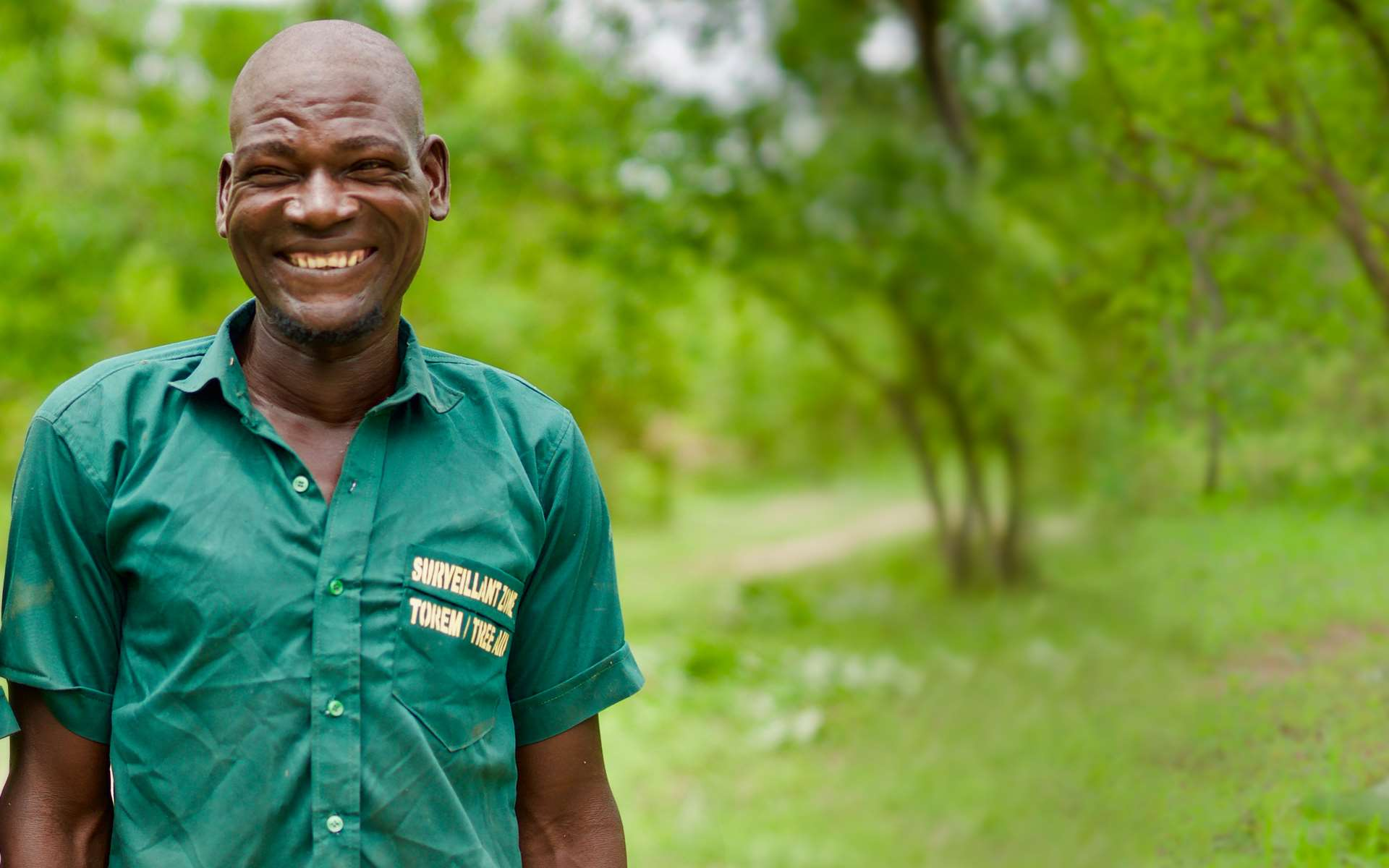 Mouni, a volunteer forest guard, smiling in front of his local forest.