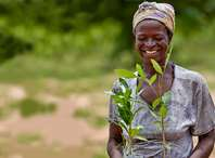 A woman smiling and holding tree saplings which she is about to plant.