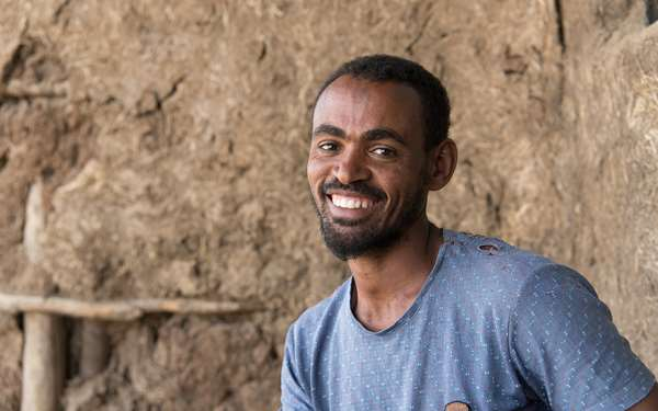 A man in Ethiopia sitting and smiling in front of a building.
