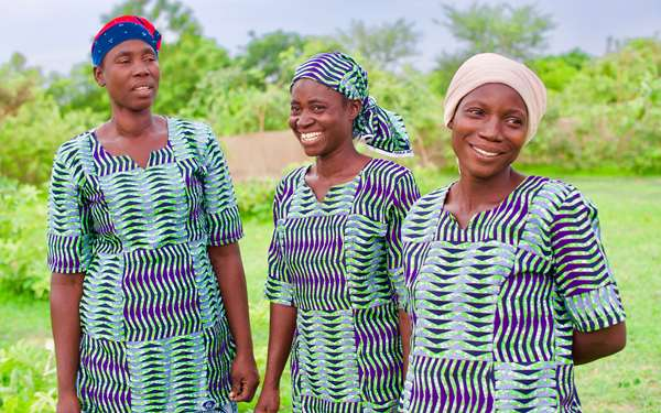 Women in a shea enterprise group smiling and laughing.