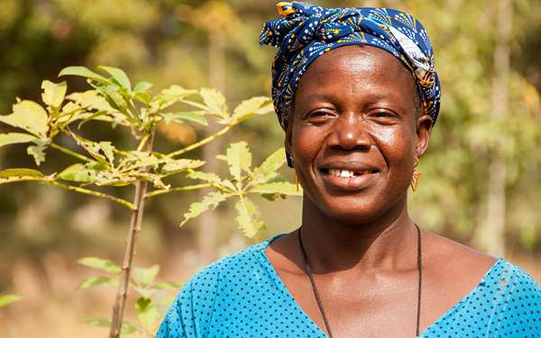 Bernadette, a women in Mali, smiling in front of trees.
