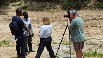 ITV News correspondent, Penny Marshall along with a cameraman interview Tree Aid project participants in Ghana in a dry, arid field