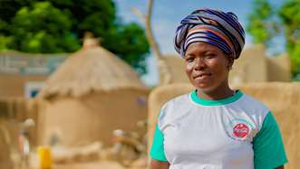 Azara, the lead secretary of a shea butter enterprise group supported by Tree Aid in Burkina Faso, stood in front of a building in her community.