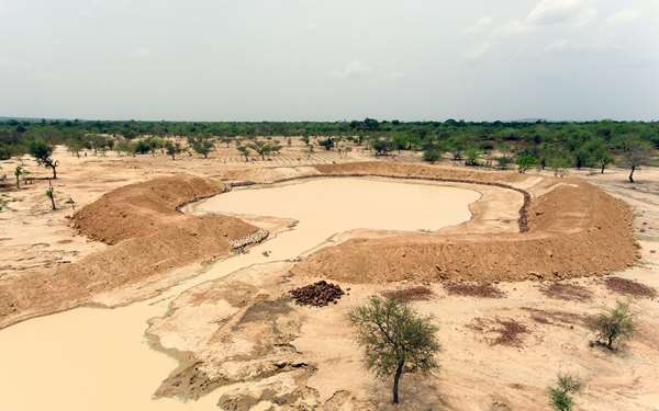 An aerial shot of a large pit of water in the land surrounded by trees - this is a bouli.