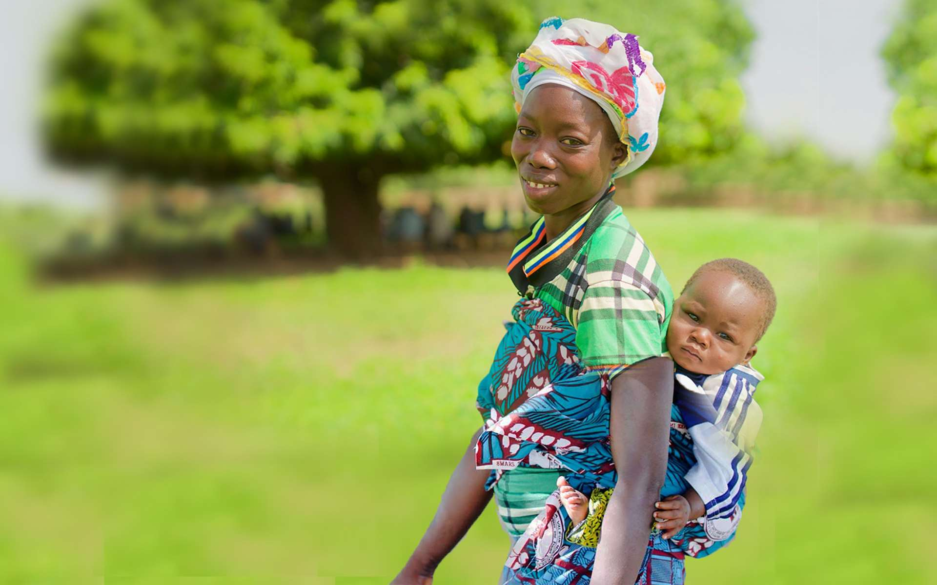 Kabouga, a woman on a Tree Aid enterprise project, with her baby on her back in front of a tree in her village.