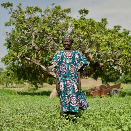 Katiana, aged 90 and the oldest women in her village in Burkina Faso, standing in front of a large tree.